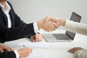 Employment handshake concept, female hr and successful woman candidate shaking hands getting hired ready to sign job contract concept, employer congratulating welcoming new worker, close up view